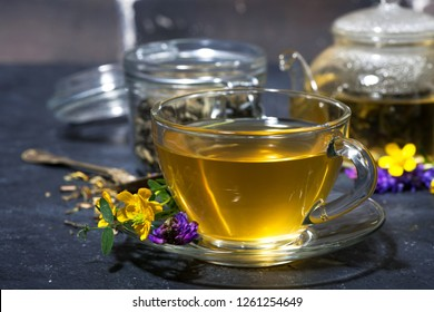 cup of fresh tea with aromatic herbs on a dark background, closeup horizontal