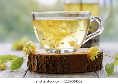 Cup of fresh tea from linden leaves in transparent dishes on a wooden stand, close-up