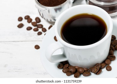 cup of freshly brewed black coffee on a white table, top view