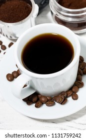 cup of freshly brewed black coffee on a white table, top view vertical