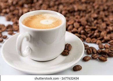 Cup with freshly brewed coffee and grains scattered next to it on a white background. Close-up.