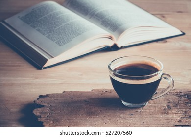 a cup of freshly coffee on a table with books