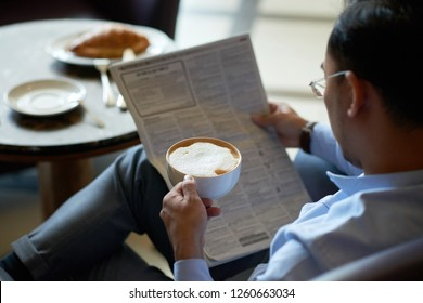 Cup of frothy creamy latte in hand of businessman reading newspaper