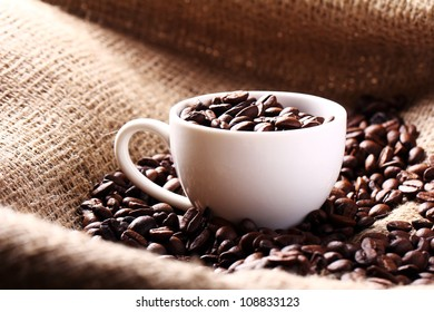 Cup full of coffee beans on the cloth sack