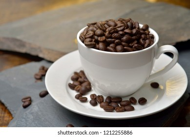 Cup full of coffee beans on the stone.