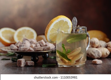 Cup of ginger tea with brown sugar , lemon and mint on old wooden table .