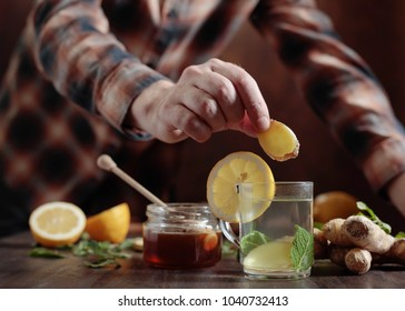 Cup of ginger tea with honey , lemon and mint on old wooden table .  Selective focus .