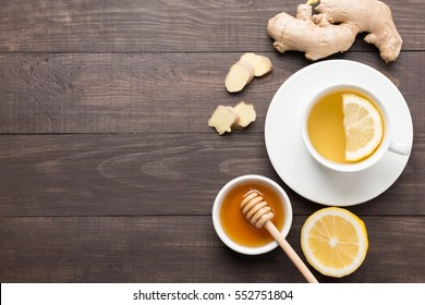 Cup of ginger tea with lemon and honey on wooden background. Copyspace for your text.
