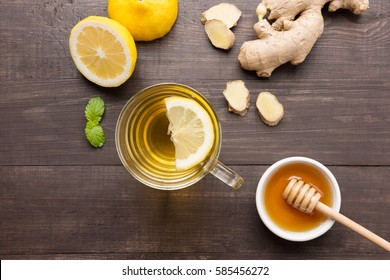 Cup of ginger tea with lemon, ginger, honey on wooden background.