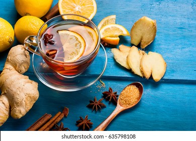 Cup of Ginger tea with lemon and honey on dark blue background, top view