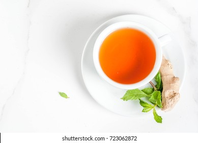 Cup of ginger tea with lemon,fresh mint and honey, on white marble table, copy space top view