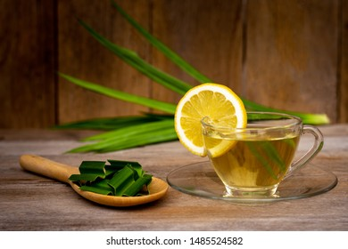 Cup glass of fresh pandan leaf ice tea or pandan juice with leaf and yellow lemon isolated on rustic wood table background. Natural herbal plant and healthy drinks concept.