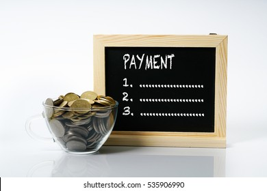 Cup glass with full coins and black board. Financial concept.