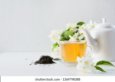 Cup of green jasmin tea white jasmine flowers, teapot on white background. Copy space. Teatime.