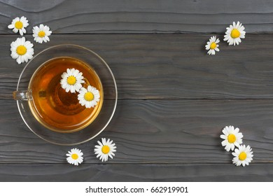 cup of green tea with chamomile on old wooden table. top view with copy space