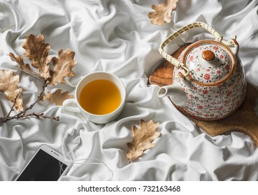 Cup of green tea, headphones, player, teapot in bed, top view. Lazy morning, warm autumn mood. Flat lay