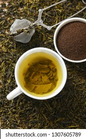 Cup of green tea and heap of dried organic tea leaves, dust and infuser  Munnar, Kerala, India. Aromatic herbal Indian beverage for relaxation, stress relief. healthy drink has antioxidants, nutrients