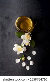 Cup of green tea and Jasmine flowerson a black background. Herbal medicine