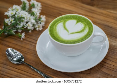 Cup of green tea latte on wooden table