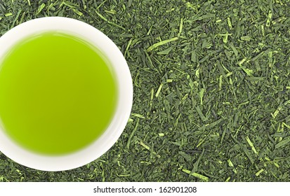Cup of green tea and green tea leaves background