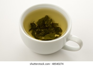 cup of green tea with leaves floating isolated on wite