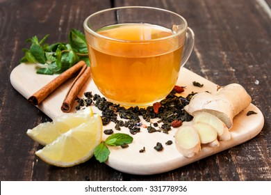 cup of green tea with lemon, ginger, cinnamon and mint