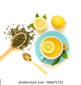 Cup of green tea with lemon and ingredients isolated on white background. View from above.