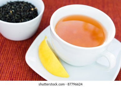 Cup of green tea with lemon on side.