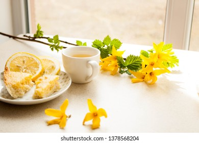 A cup of green tea with a lemon pie and yellow flowers