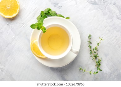 A cup of green tea with lemon, shot from the top with mint, thyme, and a place for text