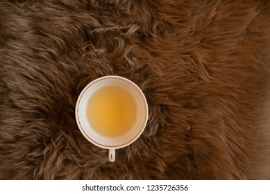 A cup of green tea on the fluffy brown fur plaid. Flat lay, top view, great for bloggers, copy space.