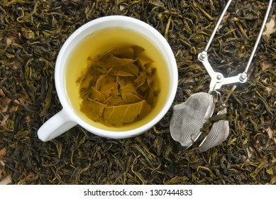 Cup of green tea on pile of dried organic green tea leaves with strainer Munnar, Kerala, India. Aromatic herbal Indian beverage for relaxation, stress relief. healthy drink has antioxidants, nutrients
