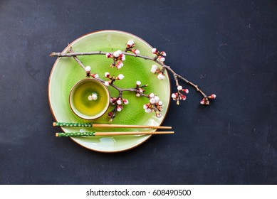 Cup of green tea and peach blossom on dark rustic table as a spring time concept