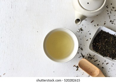 cup with green tea and teapot on white wooden table background. over light
