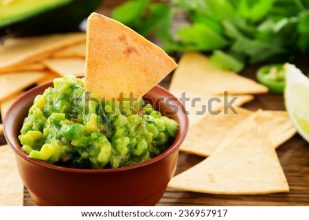 cup with guacamole and corn chips - traditional Mexican appetizer