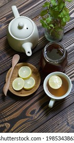 a cup of healthy drink on wooden background. Ingredient honey, lemon and tea