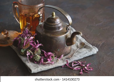 Cup of healthy echinacea tea, dry coneflower herbs and vintage teapot.