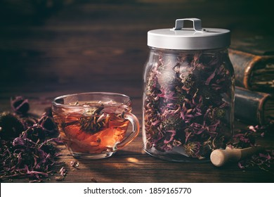 Cup of healthy echinacea tea, glass jar of dry coneflower herbs and old books on table.