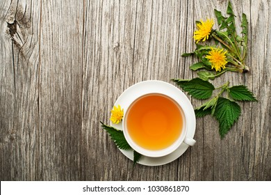Cup of healthy herbal tea with dandelion and nettle on wooden background. Herbal medicine
