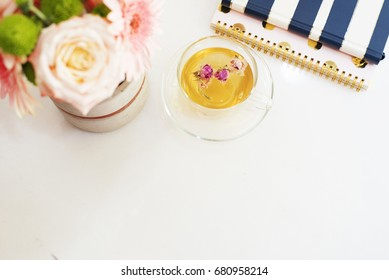 A cup of healthy herbal tea with dried roses. Beautiful fresh flowers, notebooks on light marble table, top view. Pink roses and gerberas on a female work desk. Blogger lifestyle. Floral frame