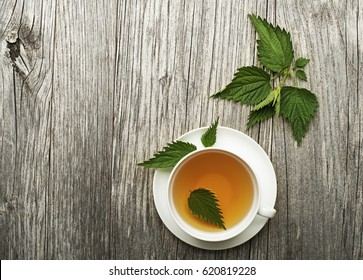 Cup of healthy herbal tea with nettle on wooden background.