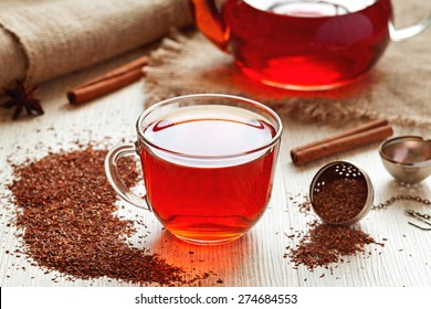 Cup of healthy traditional herbal rooibos red beverage tea with spices on vintage wooden table