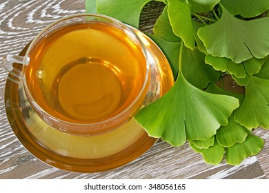 Cup of herb tea with fresh ginkgo leaves on wooden background
