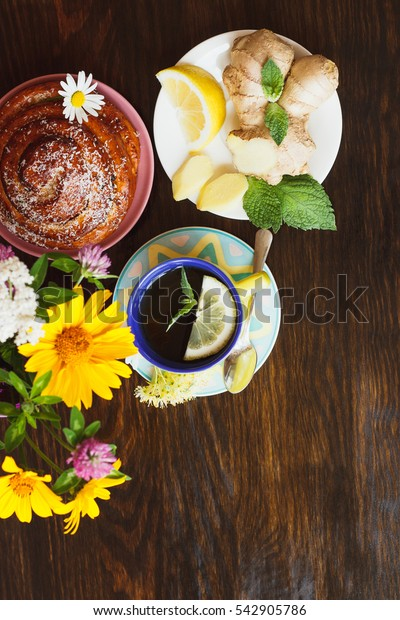 Cup of herb tea with lemon and mint leaves, ginger root and bun on the wooden background