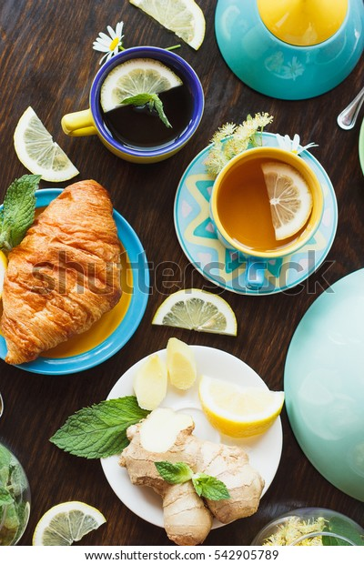 Cup of herb tea with lemon and mint leaves, ginger root and croissant on the wooden background