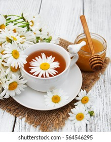 cup of herbal tea with chamomile flowers on a wooden table