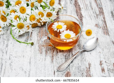 Cup of herbal tea and chamomile on the table
