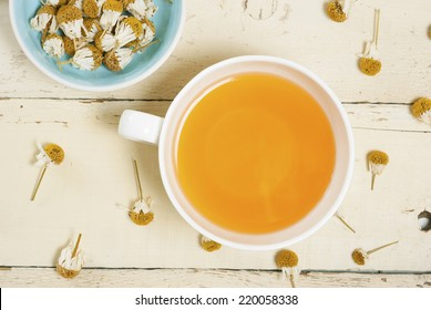 cup of herbal tea and dried chamomiles on rusty wood table