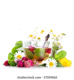 cup of herbal tea and fresh flowers on isolated white background