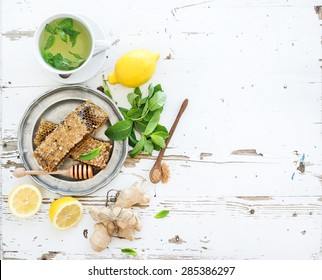 A cup of herbal tea with fresh mint, honey, lemon, ginger on rustic white wooden background. Top view, copy space